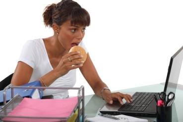 18471415 - woman eating a burger at her desk